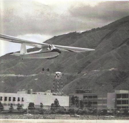 El Turpial (R1) en su vuelo inaugural, La Carlota Julio 1964. Se aprecian la guaya del winche y las ruedas usadas para despegar, ya liberados del aparato. [Archivo fotográfico de la familia Remiddi González/AVER].