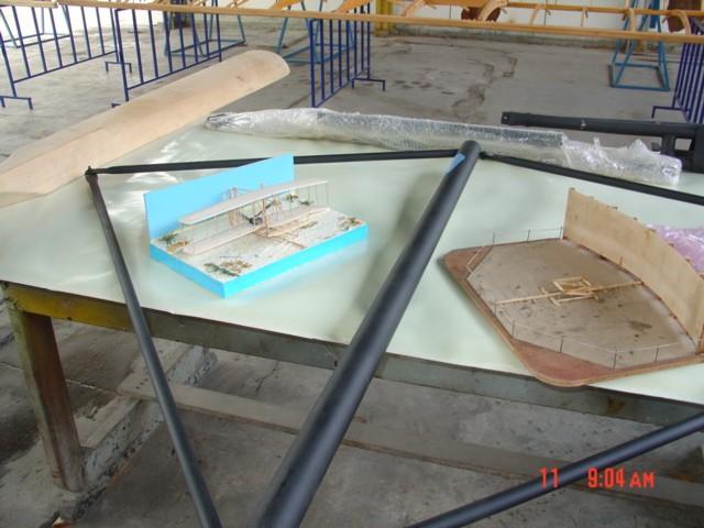 Dioramas del Flyer de 1903 en las arenas de Kitty Hawk que reflejan la propuesta de la exhibición. La pieza negra es el soporte de uno de los ejes de las hélices, la cual también está en la mesa. [Archivo fotográfico de la familia Remiddi González].