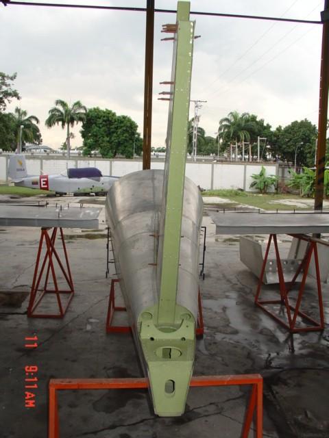 Detalle de la estructura del estabilizador vertical del Cardenal (R2). Al fondo, un avión Beech T-34 Mentor que perteneció a la EAM, y que está siendo restaurado hoy día por un grupo de voluntarios aeromodelistas. [Archivo fotográfico de la familia Remiddi González]