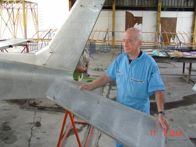 Romano Remiddi mostrando el timón de dirección del Cardenal (R2). Al fondo, componentes de la réplica del avión Flyer de 1903. [Archivo fotográfico de la familia Remiddi González]