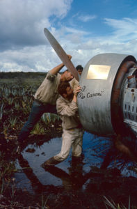 American aviator Roland Angel (center) and his cousin, Allen Waller (in blue jeans), work on Angel's father's Flamingo monoplane in a swamp, Auyantepui, Venezuela, 1965. Angel's father, aviator Jimmie Angel, was the namesake of Venezuela's Angel Falls which he first flew over in 1933, crashed this plane on a return trip in 1937, where the plane remained until 1970. Angel and Waller visited the site to attach a plaque (seen here) to the plane. (Photo by Carl Mydans/The LIFE Picture Collection/Getty Images)